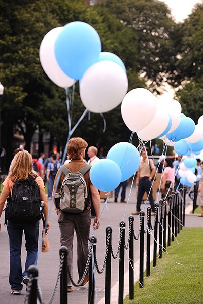 Students walking near blue and white balloon on College Walk